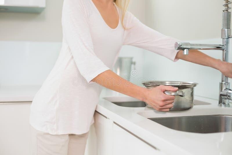 Vaso di riempimento della donna con acqua immagini stock libere da diritti