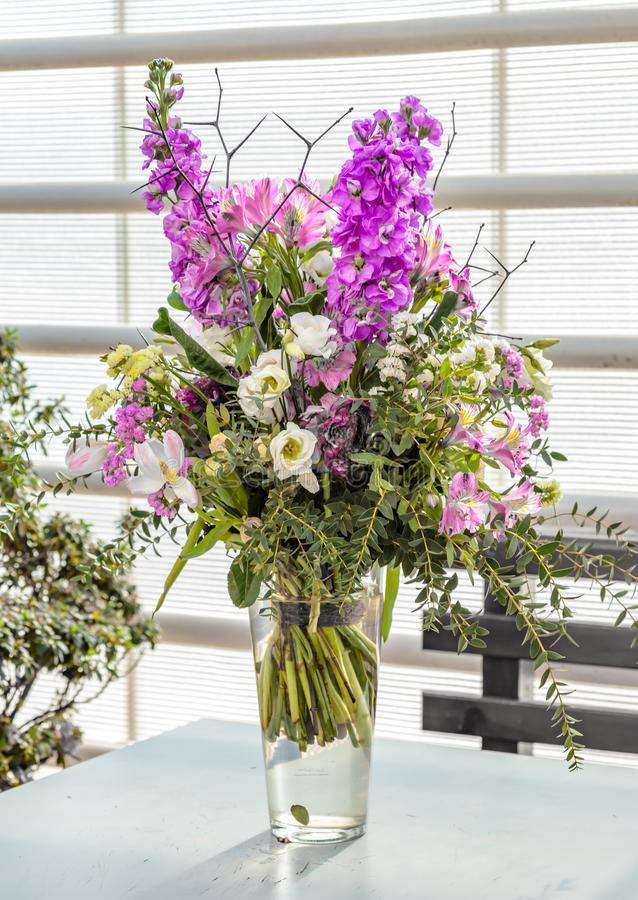 Vaso di vetro con il mazzo di bei fiori su fondo luminoso sfondo naturale della sorgente Mazzo del regalo di fiori variopinti immagine stock libera da diritti