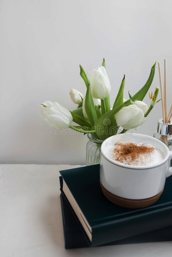 Vaso e libri di fiore lungo una tazza di caffè immagini stock libere da diritti