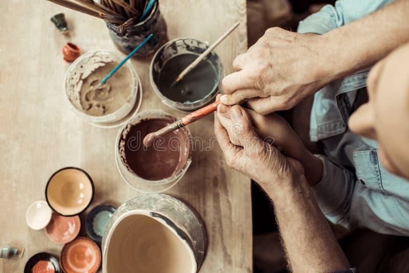 Vaso e nonni di argilla della pittura della ragazza che aiutano all'officina immagini stock