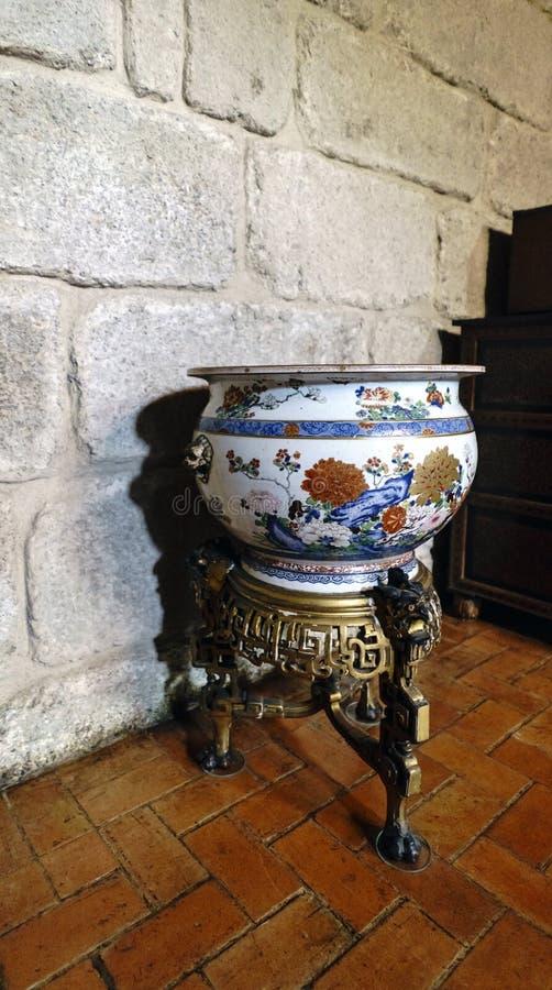 Vaso policromo cinese antico della porcellana nel rosso, nel marrone ed in blu con fondo bianco e nel supporto bronzeo nel palazz fotografia stock