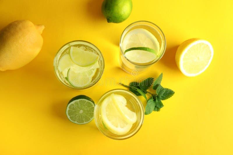 Vasos de agua con el limón y la cal en la tabla de color fotos de archivo