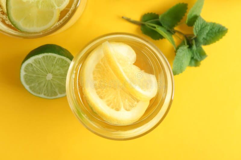 Vasos de agua con el limón y la cal en la tabla de color foto de archivo
