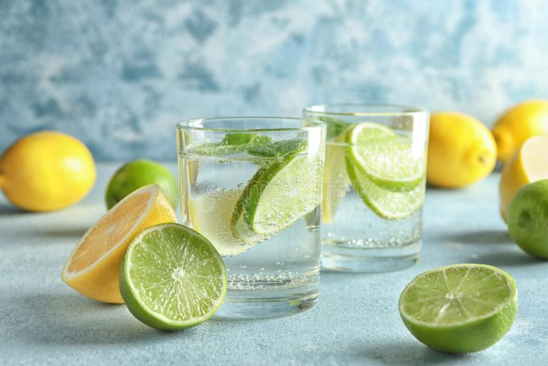 Vasos de agua con el limón y la cal en la tabla de color imagen de archivo libre de regalías