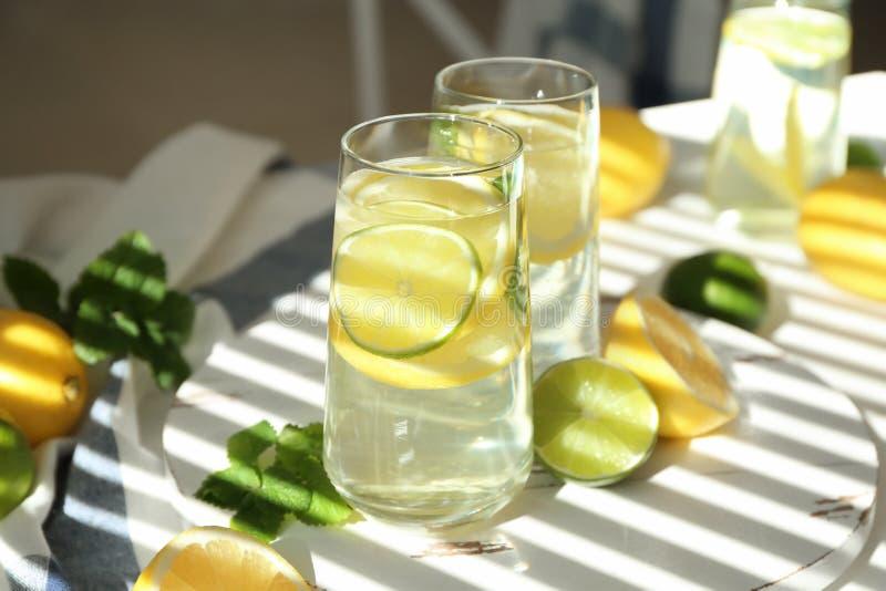 Vasos de agua con el limón y la cal en el tablero de madera imágenes de archivo libres de regalías