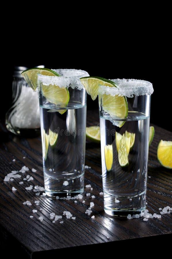 Vasos de medida altos del Tequila con la cal imágenes de archivo libres de regalías