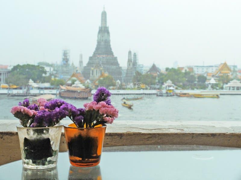 Vasos dos pares da flor com o Temple of Dawn no fundo fotografia de stock royalty free