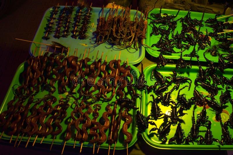 Vassoi esotici dell'alimento, scorpioni fritti, serpenti fritti e lucertole sui bastoni, scarabei cucinati immagine stock