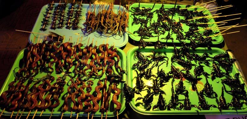 Vassoi esotici dell'alimento, scorpioni fritti, serpenti fritti e lucertole sui bastoni, scarabei cucinati fotografia stock