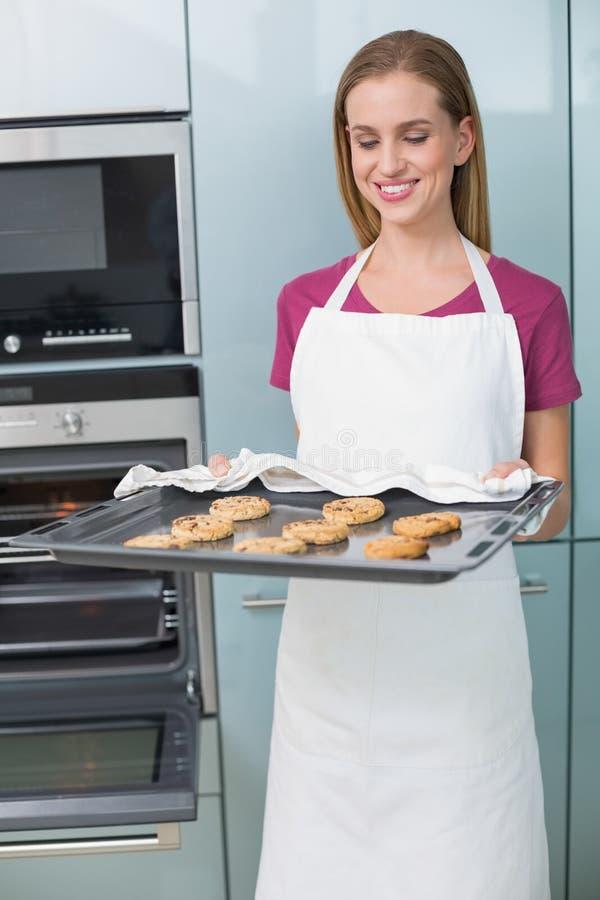 Vassoio allegro casuale di cottura della tenuta della donna con i biscotti immagini stock libere da diritti