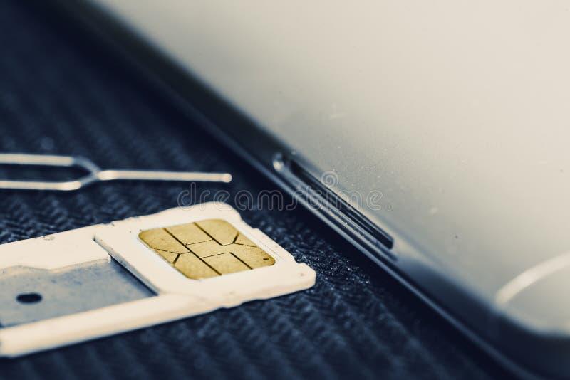 Vassoio aperto di micro Sim Card Beside Smartphone immagine stock libera da diritti