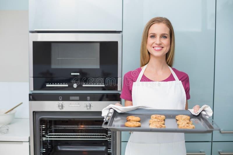 Vassoio attraente casuale di cottura della tenuta della donna con i biscotti fotografia stock
