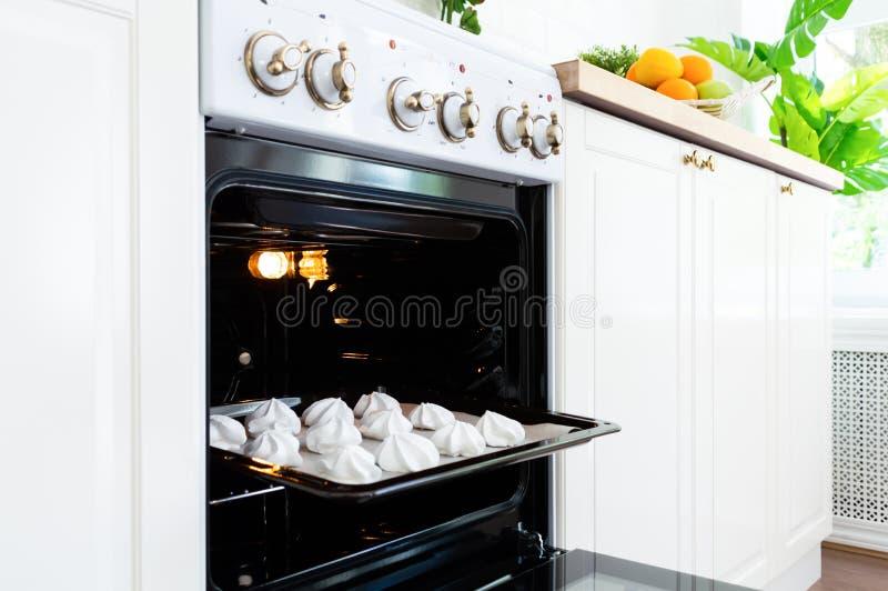 Vassoio bollente con le meringhe dolci nel forno sulla cucina fotografia stock libera da diritti