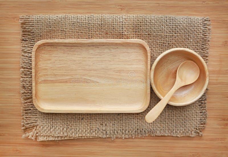 Vassoio, ciotola e cucchiaio di legno sul sacco contro il fondo di legno del bordo fotografia stock libera da diritti