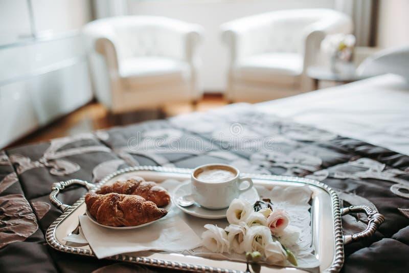 Vassoio con cappuccino, il croissant ed i fiori sul letto fotografia stock libera da diritti