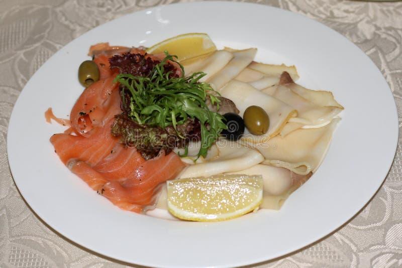 Vassoio con il pesce affettato affumicato, guarnito con il limone, le olive e l'insalata Pezzi di pesce imburrato bianco di color fotografia stock