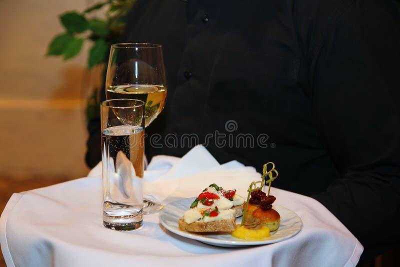Vassoio, coperto di tovaglia bianca, con un bicchiere di vino, takan con acqua e un piatto degli spuntini nella mano del camerier immagine stock