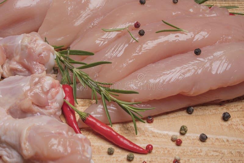 Vassoio crudo e fresco della carne di pollo su una superficie di legno con le spezie per cucinare Carne di pollo cruda sul bordo  immagine stock