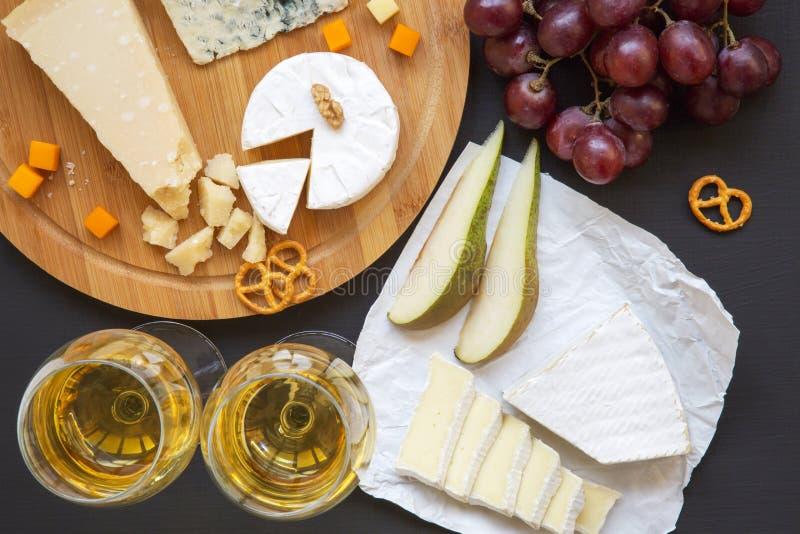 Vassoio del formaggio con vino, i frutti, le ciambelline salate e le noci su fondo scuro, da sopra immagini stock libere da diritti