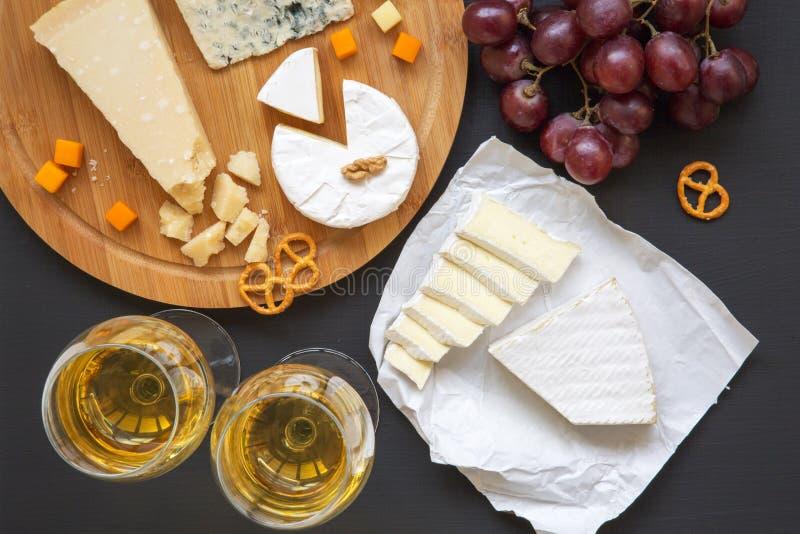 Vassoio del formaggio con vino, i frutti, le ciambelline salate e le noci su fondo scuro, da sopra fotografie stock libere da diritti