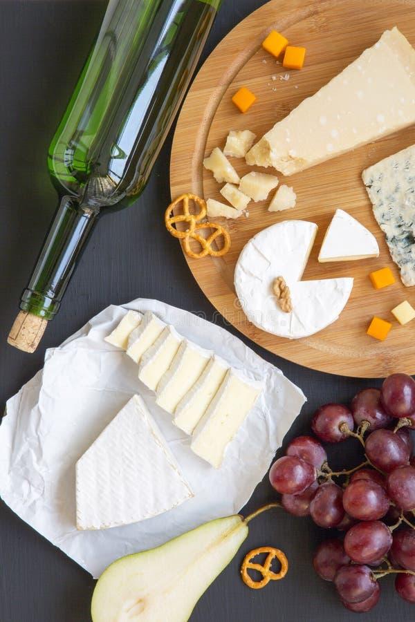 Vassoio del formaggio con vino, i frutti, le ciambelline salate e le noci su fondo scuro, vista superiore fotografia stock