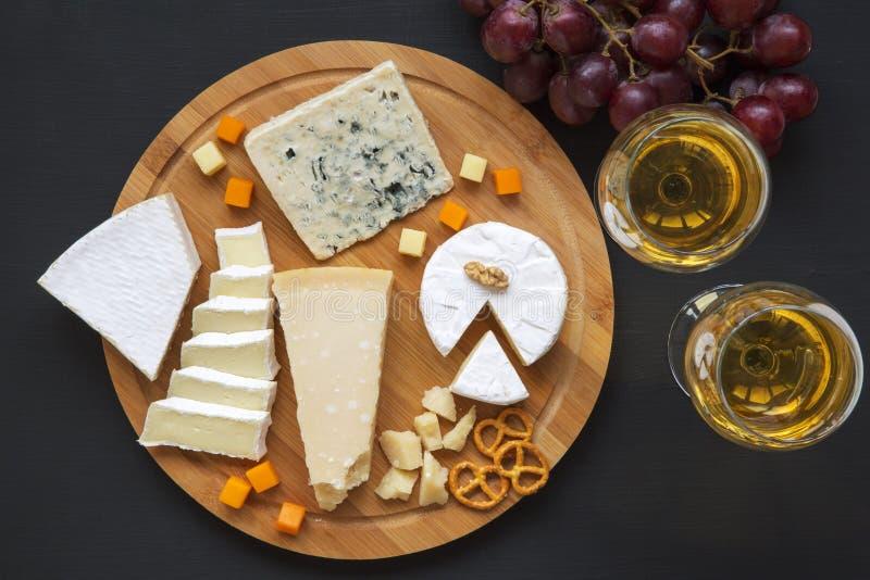 Vassoio del formaggio con vino, l'uva, le ciambelline salate e le noci su fondo scuro, da sopra Vista superiore immagine stock