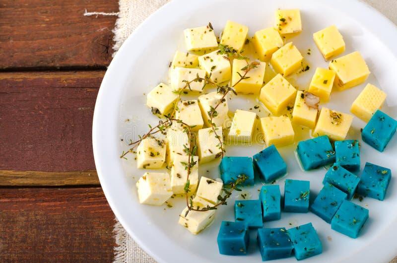 Vassoio del formaggio, gouda, feta, formaggi blu di pesto sul piatto bianco con le erbe, olio d'oliva, melograno e salse di senap fotografie stock