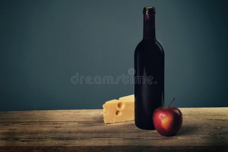 Vassoio del formaggio guarnito con miele, la mela e la bottiglia di vino sul bordo di legno rustico immagine stock