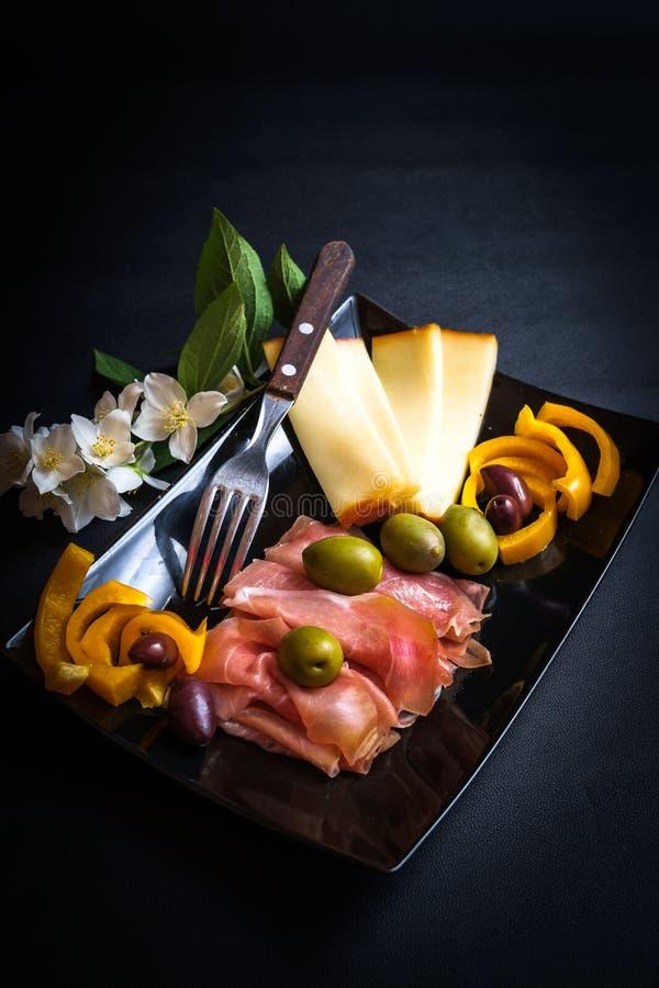 Vassoio del prosciutto di Parma, del formaggio e delle olive immagini stock