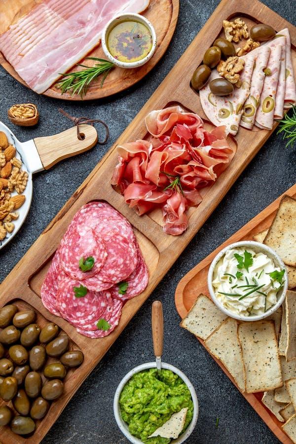Vassoio dell'antipasto Serrano del prosciutto, salse verde oliva della immersione del jamon del salame e vino rosso fotografie stock
