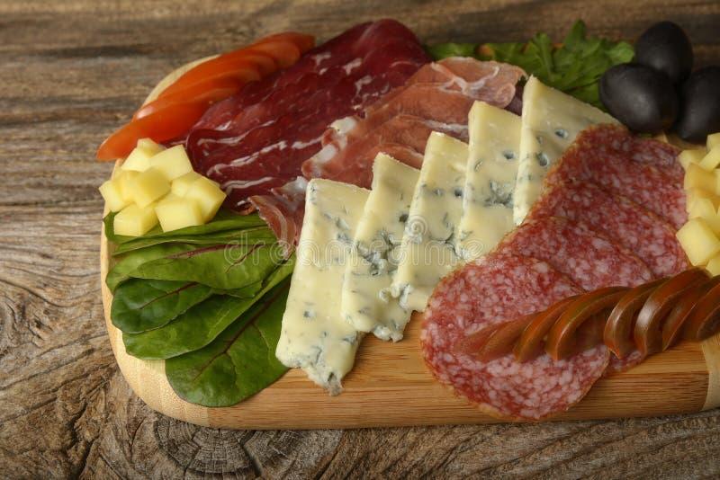 Vassoio della carne fredda e del formaggio blu con salame, il prosciutto di Parma del prosciutto delle fette, il formaggio, le ol immagine stock libera da diritti