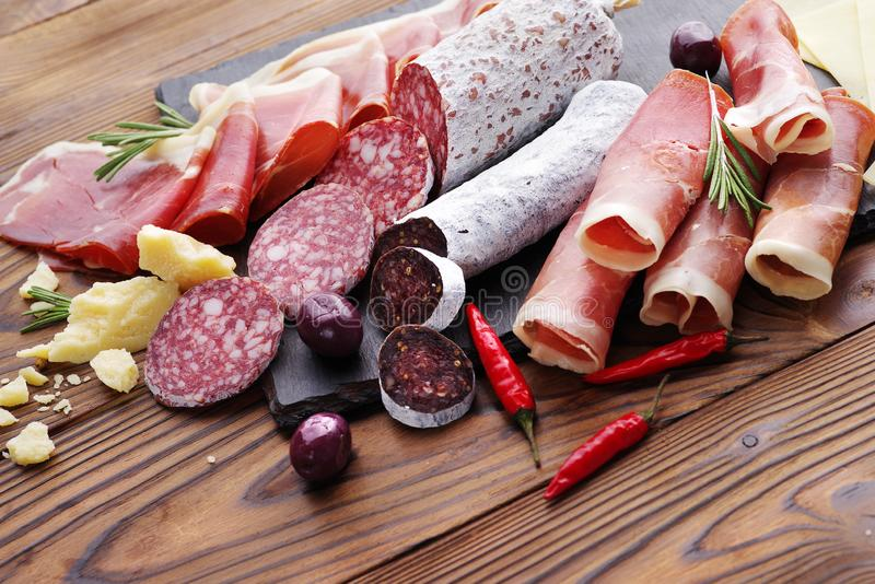 Vassoio della carne della squisitezza di jamon e del fuet spinto della salsiccia su una tavola di legno immagine stock