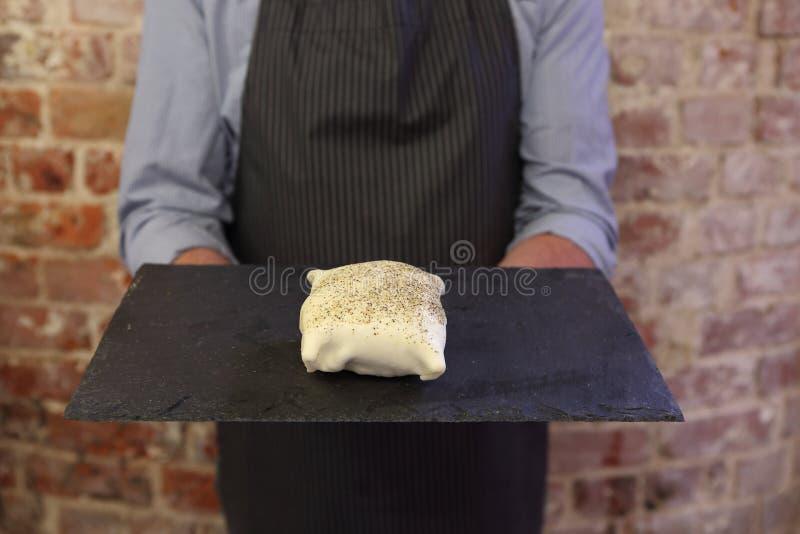 Vassoio della tenuta dell'uomo con un pacchetto crudo della pasticceria sopra immagine stock