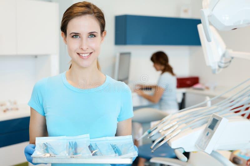 Vassoio di aiuto della tenuta con gli strumenti dentari fotografia stock libera da diritti