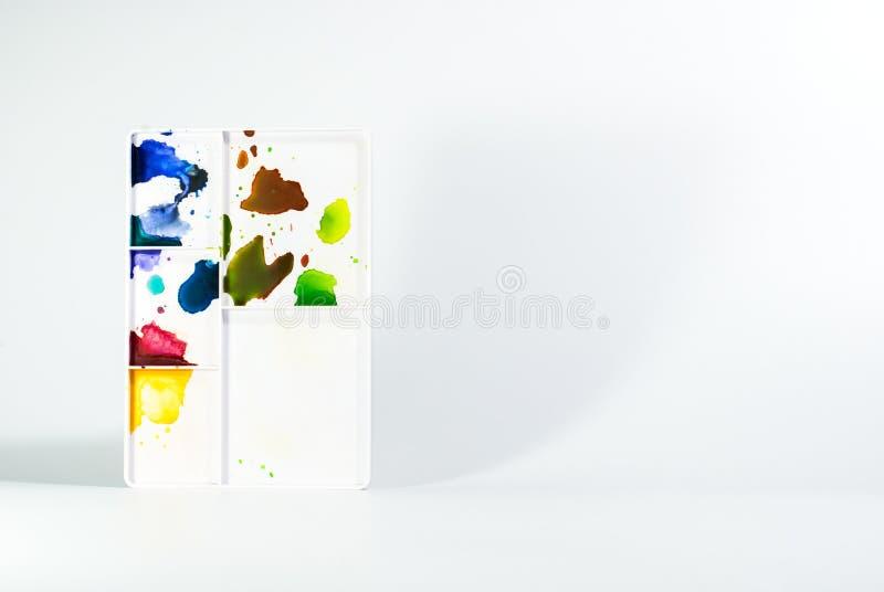 Vassoio di plastica bianco di miscelazione dell'acquerello che sta sul backgroun bianco fotografie stock libere da diritti