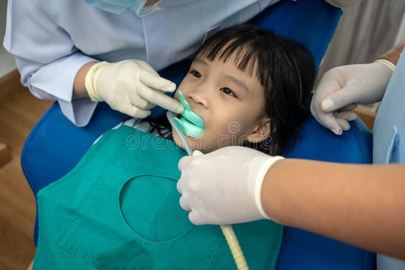 Vassoio mordente del silicio della ragazza asiatica di fluoruro e di aspirazione dentaria fotografia stock libera da diritti