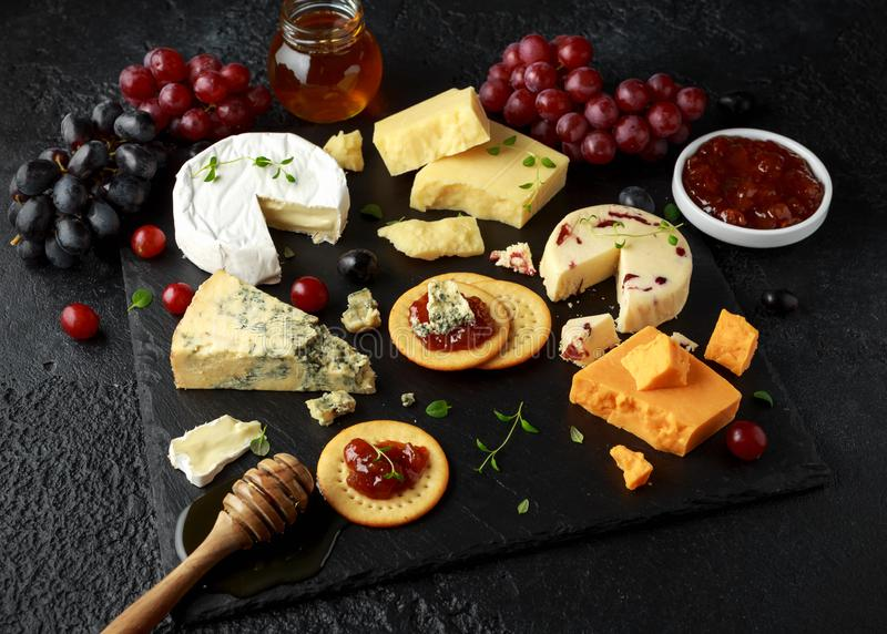 Vassoio servito con l'uva, chutney della birra inglese, miele, cracker del formaggio sul bordo di pietra Brie, cheddar, Leicester fotografie stock