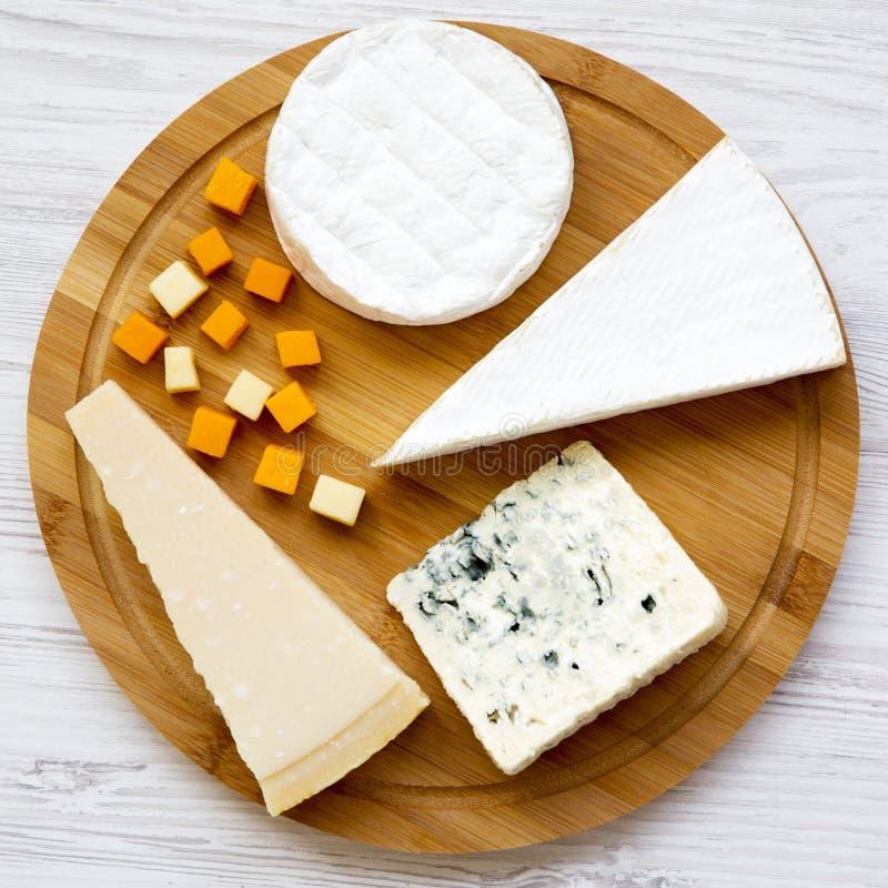 Vassoio su una tavola di legno bianca, vista superiore del formaggio Alimento per vino Disposizione piana, da sopra fotografia stock libera da diritti