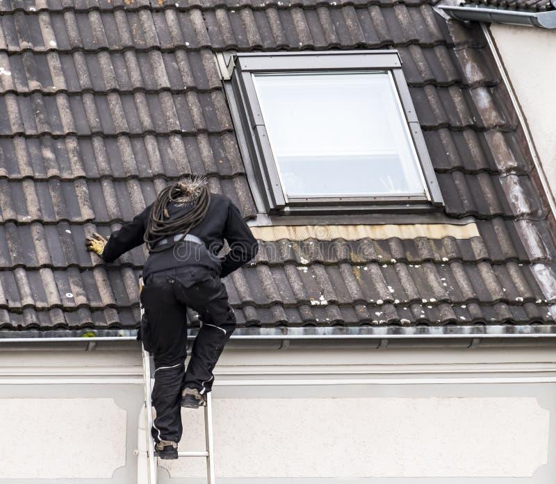 Vassoura da chaminé que escala o telhado fotos de stock