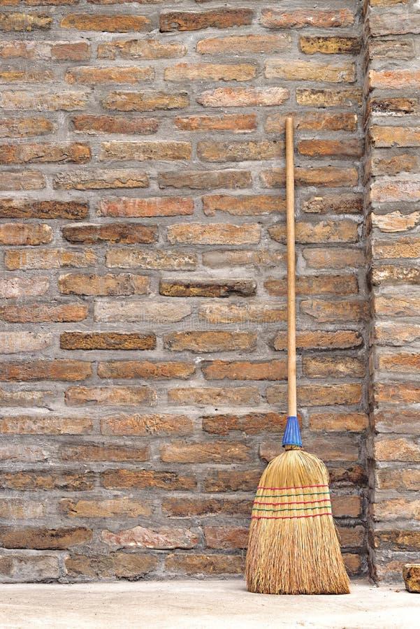 Vassoura do agregado familiar para a limpeza do assoalho que inclina-se na parede de tijolo fotografia de stock