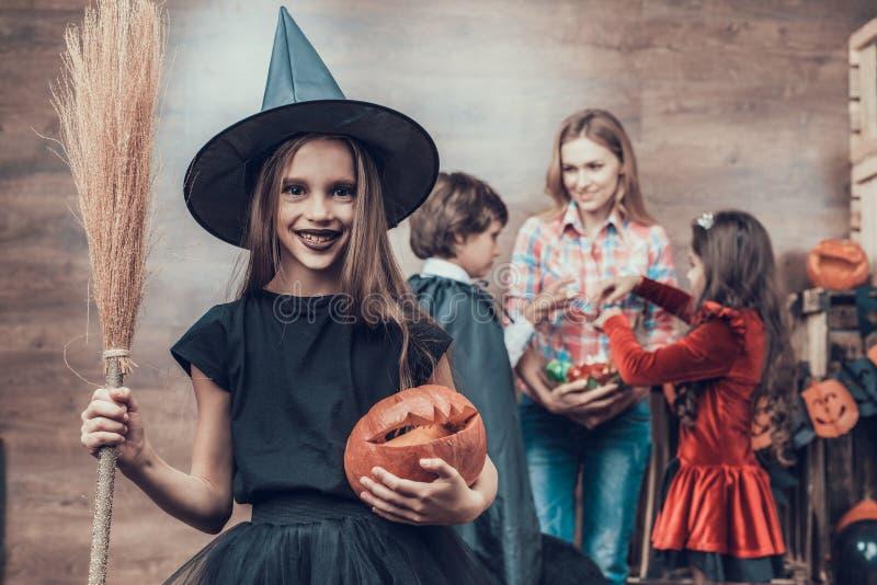 Vassoura vestindo da terra arrendada do traje da bruxa da moça fotografia de stock royalty free