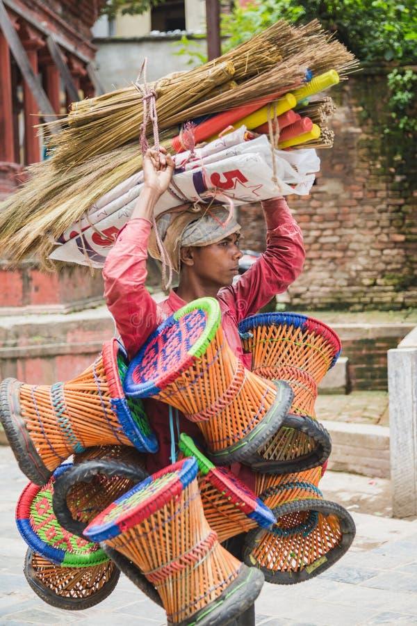 Vassouras levando do vendedor de rua e ferramentas de bambu de assento em Kathma imagens de stock royalty free
