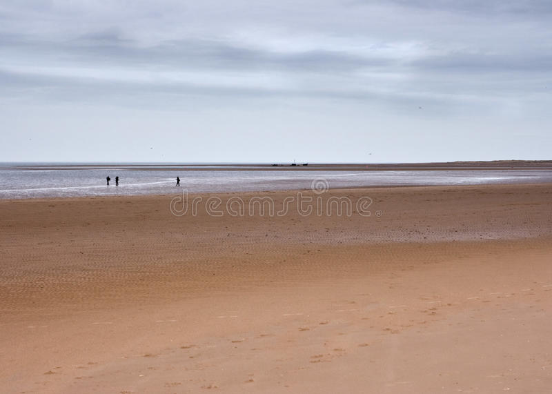Vast beach and horizon with figures, Norfolk, UK royalty free stock images