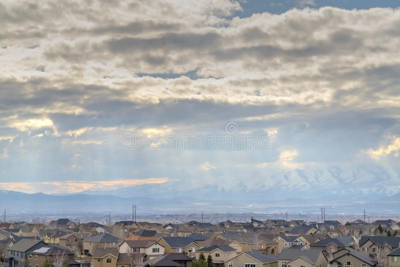 Vast blue sky filled with puffy clouds over houses in the valley. Power lines and towering snow capped mountain can also be seen in this landscape royalty free stock photography