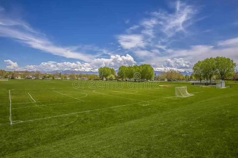 Vast sports field with soccer goal net and baseball bleachers behind a fence royalty free stock photos
