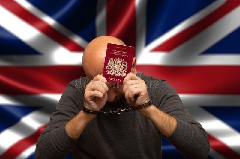 Vastgehouden burger van Engeland in handcuffs met een paspoort in zijn handen, het verbergen royalty-vrije stock foto