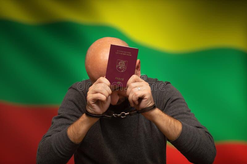 Vastgehouden burger van Litouwen in handcuffs met een paspoort in zijn handen, het verbergen royalty-vrije stock fotografie