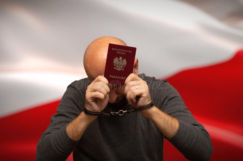 Vastgehouden Poolse burger in handcuffs met een paspoort in zijn handen, het verbergen stock foto's