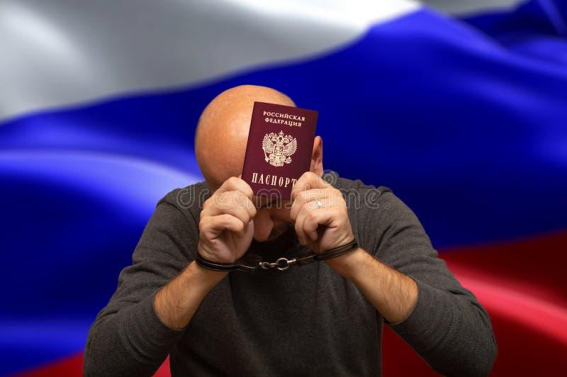 Vastgehouden Russische burger in handcuffs met een paspoort in zijn handen royalty-vrije stock foto's