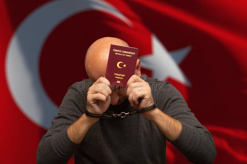 Vastgehouden Turkse burger in handcuffs met in hand paspoort royalty-vrije stock foto's